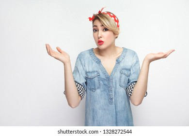 I don't know. Portrait of confused beautiful young woman in casual blue denim shirt with makeup and red headband standing, looking and dont know what to do. studio shot, isolated on white background.