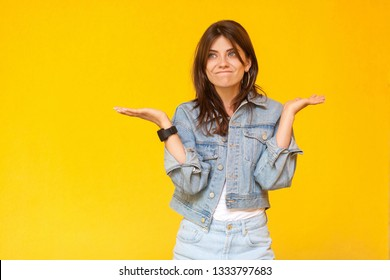 I don't know. Portrait of confused beautiful brunette young woman with makeup in denim casual style standing with raised arms, looking away and doubt. indoor studio shot, isolated on yellow background