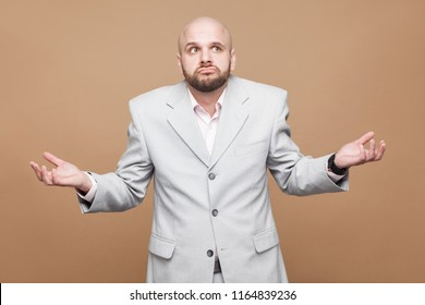 I don't know! Portrait of confused crossed hands handsome middle aged bald bearded businessman in classic light gray suit standing and thinking. indoor studio shot, isolated on light brown background.