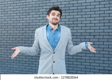 I don't know. Portrait of confused handsome bearded man in casual style standing, raised arms and looking at camera with doubtful face. indoor studio shot on brick wall background.