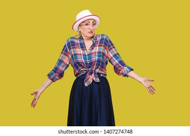 I don't know. Portrait of confused modern stylish mature woman in casual style with hat and eyeglasses standing, thinking, raised arms, looking away. indoor studio shot isolated on yellow background.