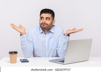 Don't know! Puzzled clueless confused businessman sitting office workplace with laptop on desk, shrugging shoulders, doubting can`t make decision. indoor studio shot isolated on white background