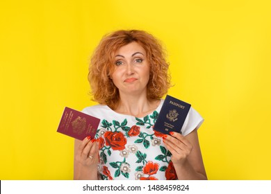 I dont know which citizenship to choose concept. Portrait young woman holding two passports one European burgundy red and American blue one confused face expression isolated on yellow wall background