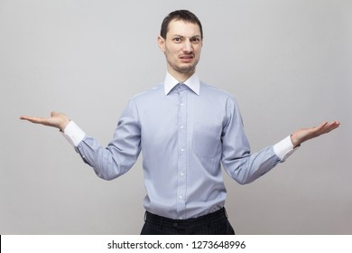 I don't know, which one to choose. Portrait of confused bristle businessman in blue shirt standing with raised arms and looking at camera. indoor studio shot, isolated on grey background copyspace.