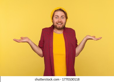 Don't know, who cares! Confused hipster bearded guy in beanie hat and checkered shirt standing with no idea gesture, shrugging shoulders raising hands. indoor studio shot isolated on yellow background