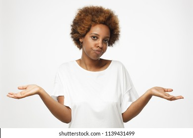 I don't know. Young afrcian american woman isolated on grey background, showing helpless gesture with arm and hands, as if he does not know what to do