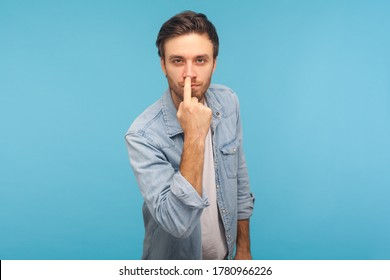 Don't lie to me! Portrait of man in worker denim shirt touching nose, showing liar gesture, angry about falsehood, outright deception, fake news. indoor studio shot isolated on blue background