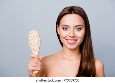 I don't lose hair anymore! Close up portrait of happy satisfied beautiful girl with shiny smile, she is showing a comb without hairs on it, isolated on grey background
