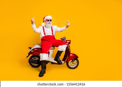 Don't need your advises! Full body photo of crazy white hair santa sitting bike showing impolite gestures wear sun specs pants cap shirt boots isolated yellow color background