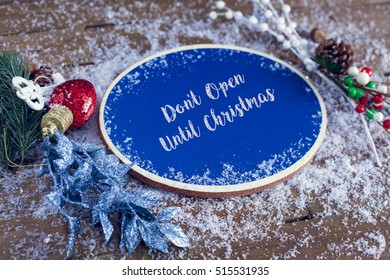 Don't Open Until Christmas Written In Chalk On Blue Chalkboard Holiday Sign Background With Snow And Decorations.