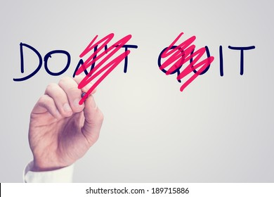 Don't Quit - Do It, conceptual image with a man scrubbing through letters in the words Don't Quit converting them to Do It with a red pen in a motivational message of hope and perseverance.