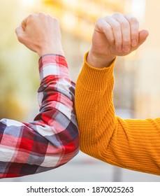 Don't shake hands. Stop handshakes. Coronavirus epidemic. Coronavirus, illness, infection, quarantine, COVID-19. Elbow bump. Bump elbows. Friends shaking elbows outdoors. Elbow greeting style.