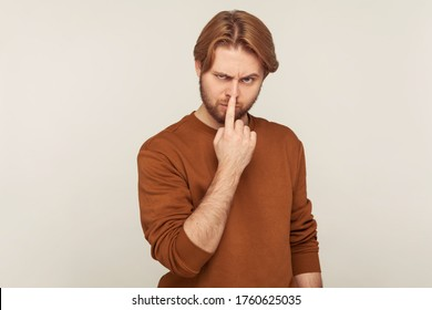 Don't tell lie! Portrait of angry bearded man in sweatshirt touching nose with finger, showing liar gesture, suspecting deception, falsehood in communication. studio shot isolated on gray background