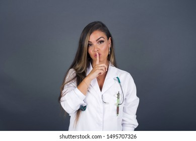 Dont tell my secret or not speak too loud, please! Emotional surprised doctor makes hush gesture, asks be quiet, poses against gray studio wall.