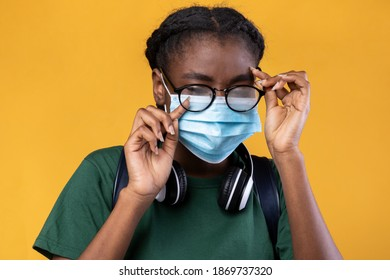 Don't Touch Your Face. Black Female Student Wearing Medical Mask And Scratching Eye Standing Over Yellow Studio Background. Covid-19 Pandemic Outbreak, Coronavirus Protection