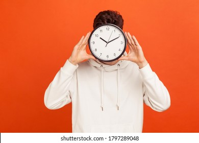 Don't waist your time! Man in casual white sweatshirt holding wall clock hiding his face, time management, schedule and meeting appointment. Indoor studio shot isolated on orange background