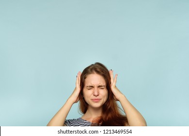 don't want to hear it. rejection refusal and denial. young woman covering ears with hands. portrait of a girl with tightly shut eyes on blue background.