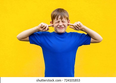 I don't want hear you! Sadness ginger boy holding fingers on ears and   closed eyes. Isolated on yellow background