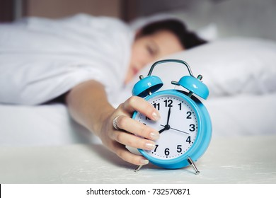 Dont want Wake up in the morning, Defocus Woman sleep on bedroom, Time 8 o clock am, sleepy and lazy,getting out of bed. Girl catch and stop snooze alarm by hand