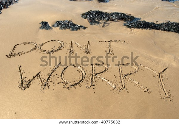 dont worry inscribed on the beach with waves in the background on a hot sunny day