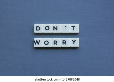 ' Don't Worry ' word made of square letter word on grey background.