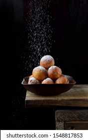 Donut balls in a clay bowl sprinkled with sugar powder on the edge of the wooden table against black background