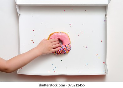 Donut box with a young female child's hand reaching to grab the last pink strawberry frosted doughnut