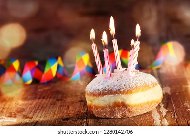 Donut with candles and colorful carnival decoration on rustic wood