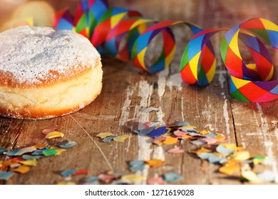 Donut with colorful carnival decoration on rustic wooden table
