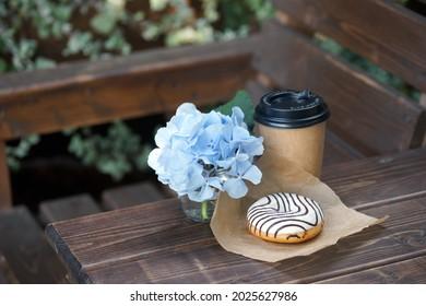 Du Donut et du verre artisanal avec un verre sur une table en bois à l'extérieur