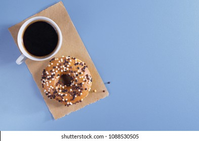 Donut decorated with white and dark chocolate balls and cup of coffee on paper is located on a blue table, top view with space for text