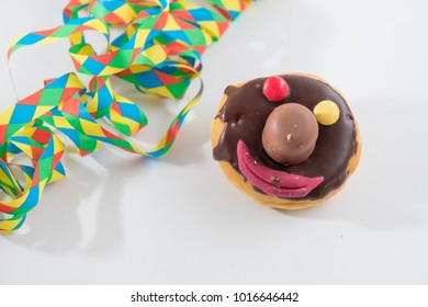 Donut with funny face on a white background with streamers