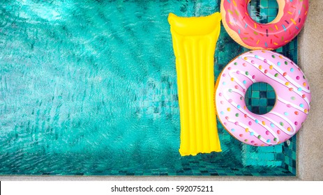 Donut lilo in the poolside at private villa. Inflatable ring and mattress. Summer holiday idyllic. High view from above.