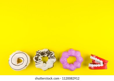 Donut made at home and red plastic wind up chattering teeth on yellow background same concept with pacman game.High energy foods to work.Foods with very high calories, sugars