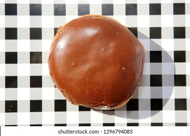Donut. Donut on a black and white checker tray. Isolated on white. Room for text. Cream Filled Chocolate Covered Donut. Bavarian Cream Filled donut.