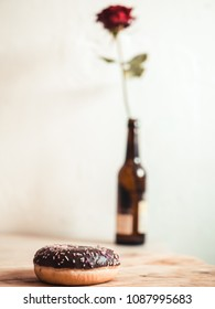 Donut on wooden board with red rose in background