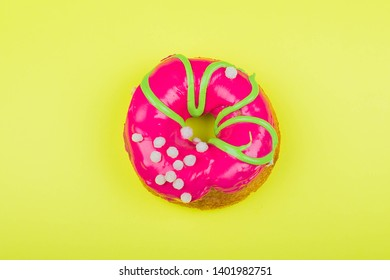 Donut with red glaze on a yellow background, close-up