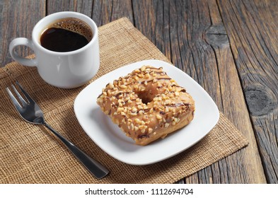 Donut in shape of square with a caramel glaze, roasted nuts and chocolate stripes in plate and cup of coffe on the old wooden table
