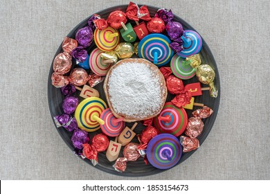 Donut, spinning tops, wooden dreidels, candies for Jewish holiday Hanukkah on dark plate over cotton fabric background. Top view.