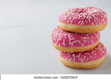 Donut. Sweet icing sugar food. Dessert colorful snack.Treat from delicious pastry breakfast. Bakery cake. Doughnut with frosting. Baked unhealthy round on a blue background. with copy space