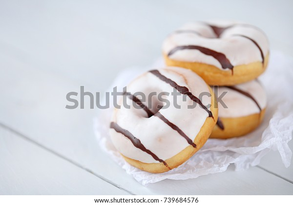 Donut. Three white striped donuts on white paper on a light wooden plank background. tasty glazed striped donut
