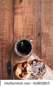 Donuts and black coffee over rustic background. Image shot from overhead.