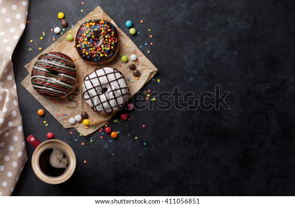 Donuts and coffee on stone table. Top view with copy space