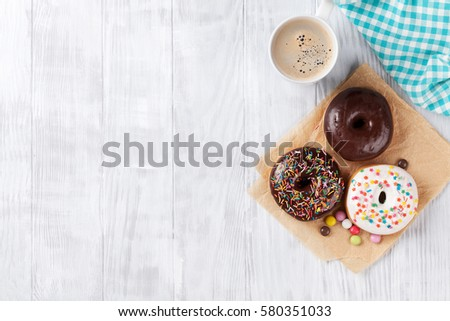 Donuts and coffee on wooden table. Top view with copy space