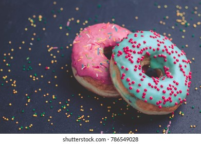 Donuts with colorful icing on a dark background.