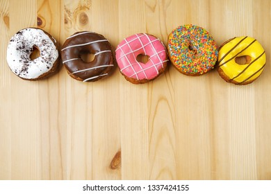 Donuts and confetti on a wooden table with space for your text. Diet concept.