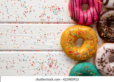 donuts in different glazes on wooden white background and space for text