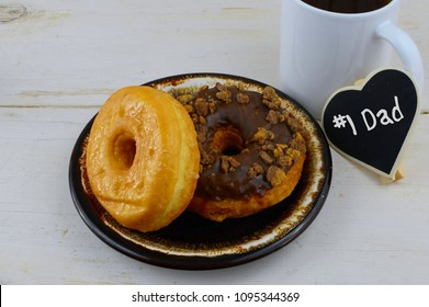 Donuts, or doughnuts, on a brown ceramic plate with a cup of coffee on a whitewahed rustic table top. Good image for donuts and dads for father's day in June.