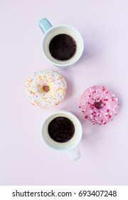 Donuts with icing and cup of espresso on colorful background.
