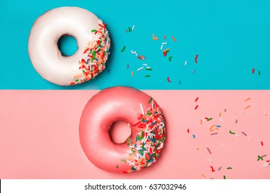 Donuts with icing on colorblock background. Sweet donuts.
